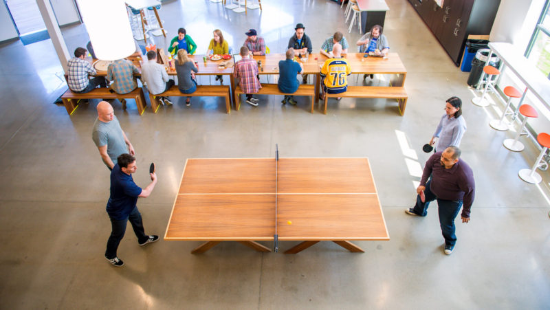 Rustici staff playing ping pong and eating lunch